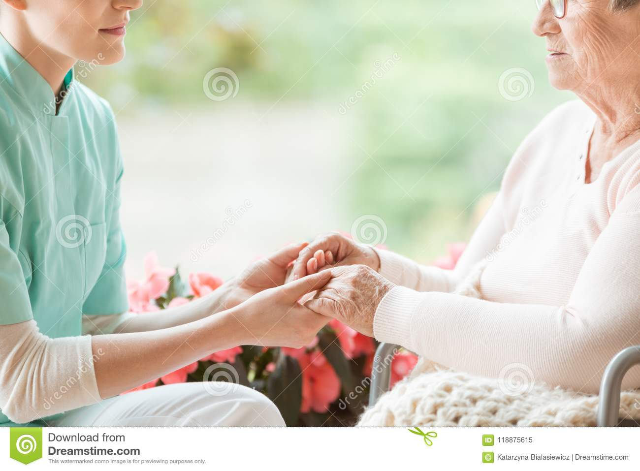 Nurse holding hands of disabled elderly woman