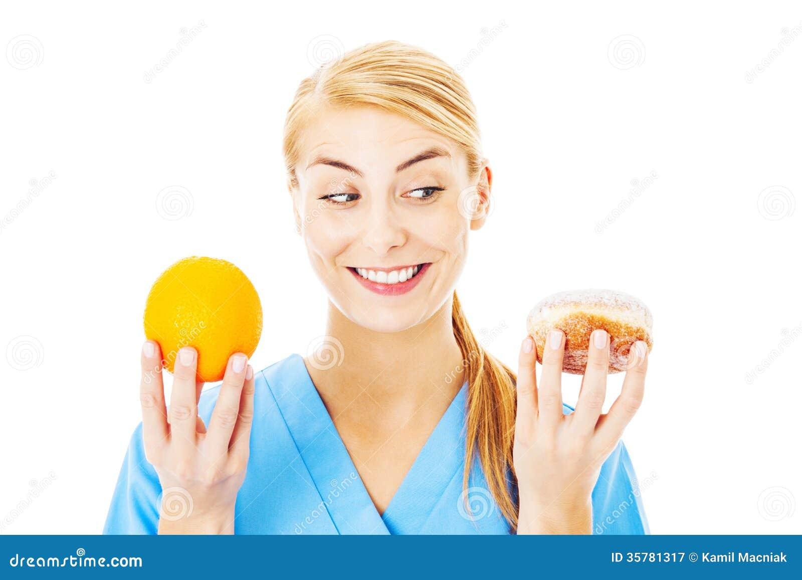 Nurse Holding Sweet Food And Orange Over White Background