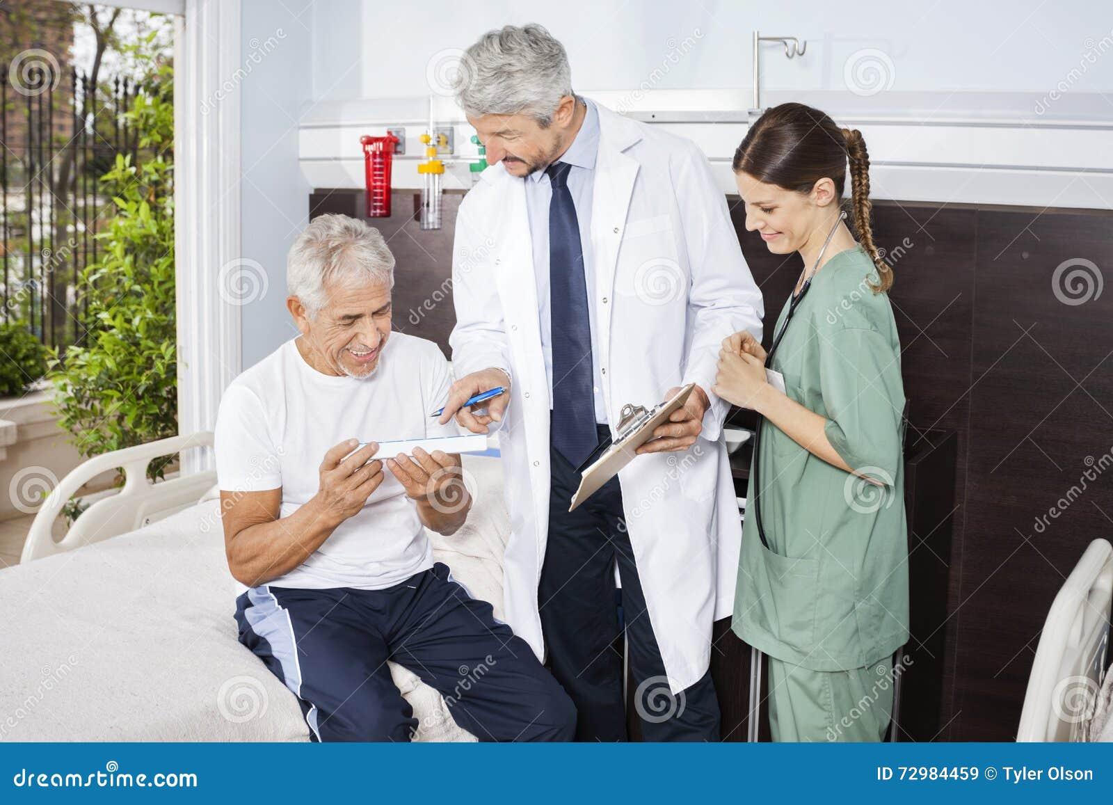 Nurse Looking At Doctor Explaining Prescription To Patient