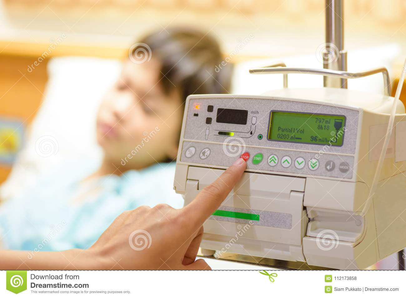 Nurse`s hand pressing on infusion pump intravenous IV drip