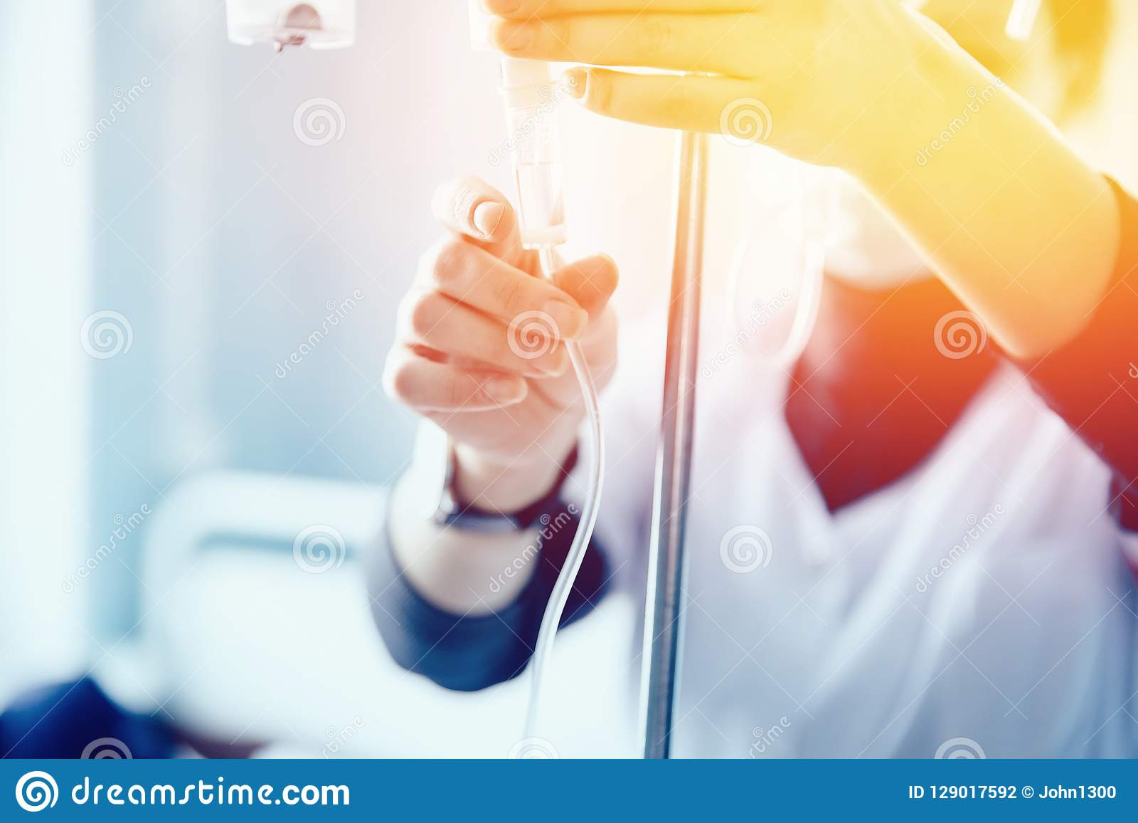 Nurse sets the patient`s dropper