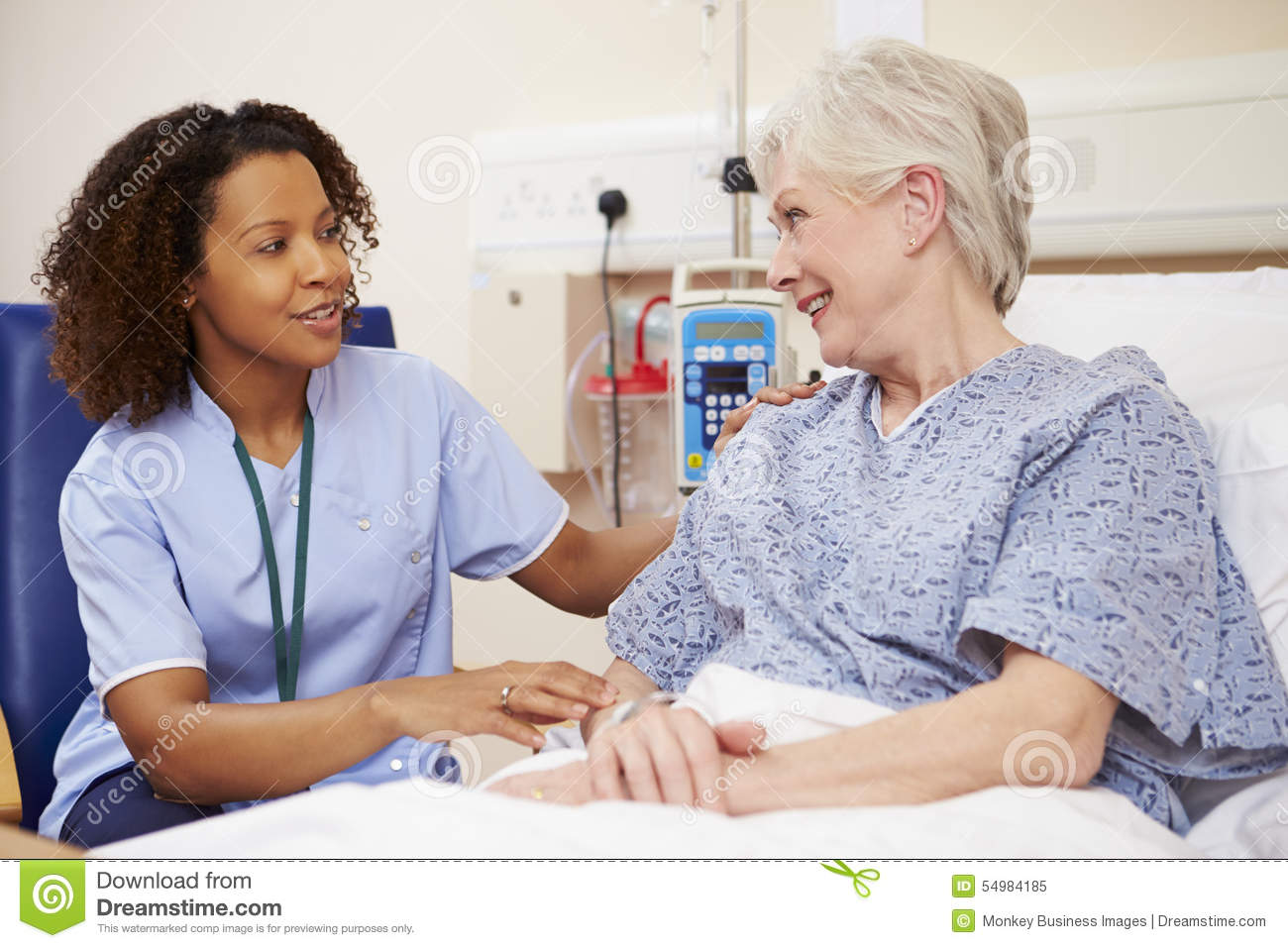 Nurse Sitting By Female Patient s Bed In Hospital