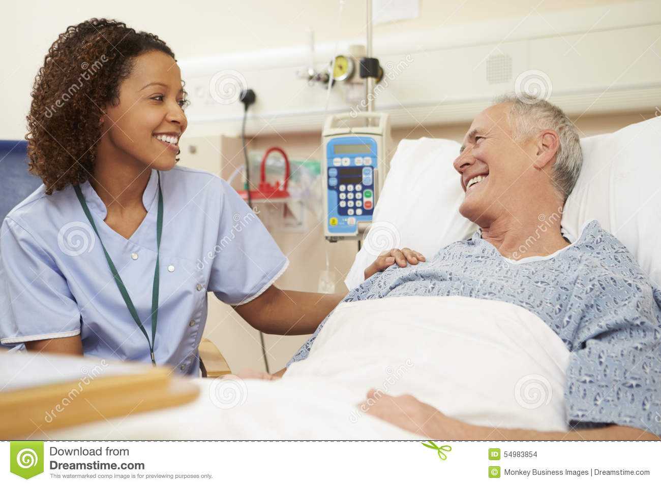 nurse sitting by male patients bed in hospital stock