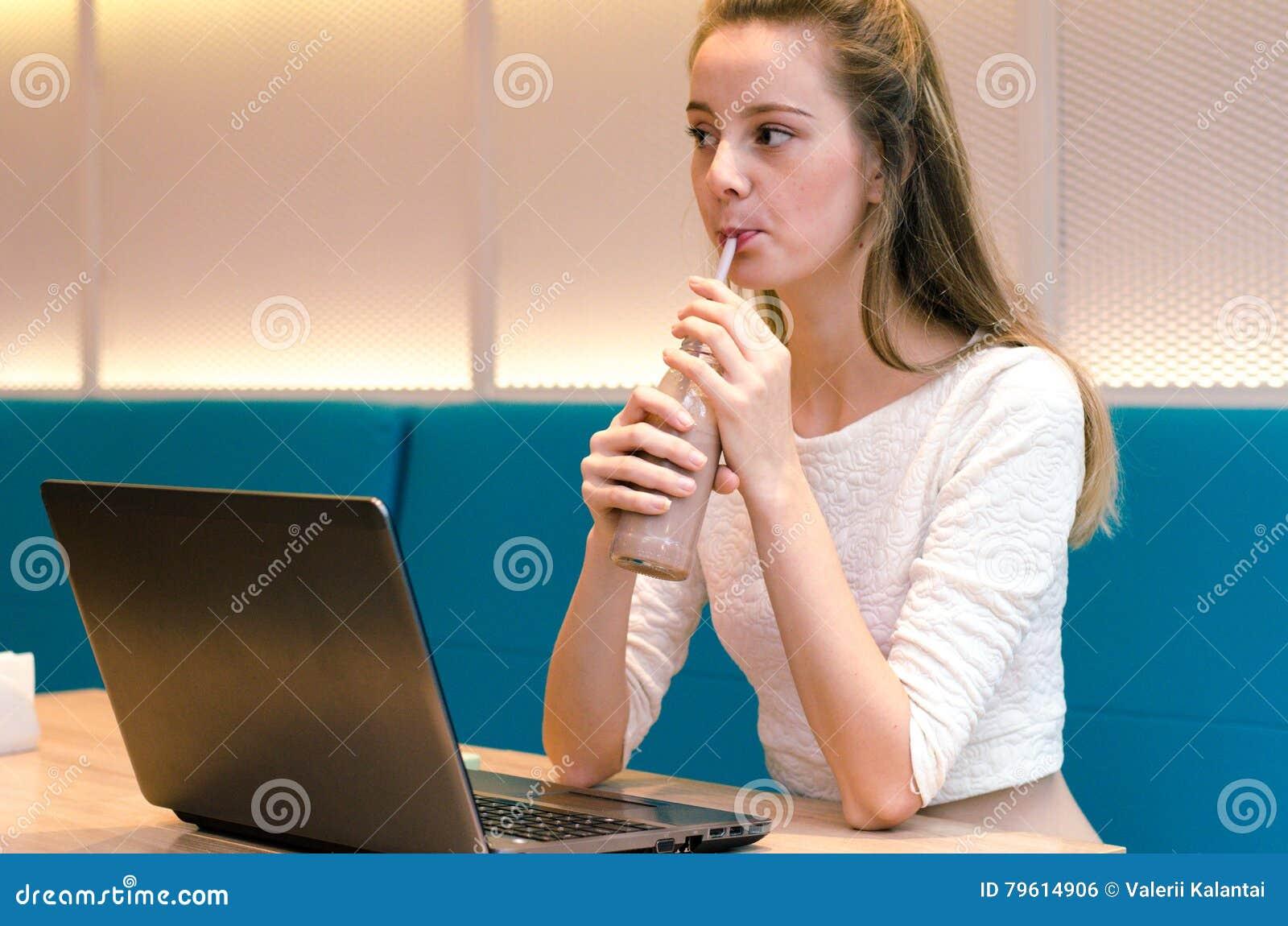 Nutrição de Juice And Smoothies For Healthy da desintoxicação Mulher de sorriso bonita que senta-se na cozinha com desintoxicação