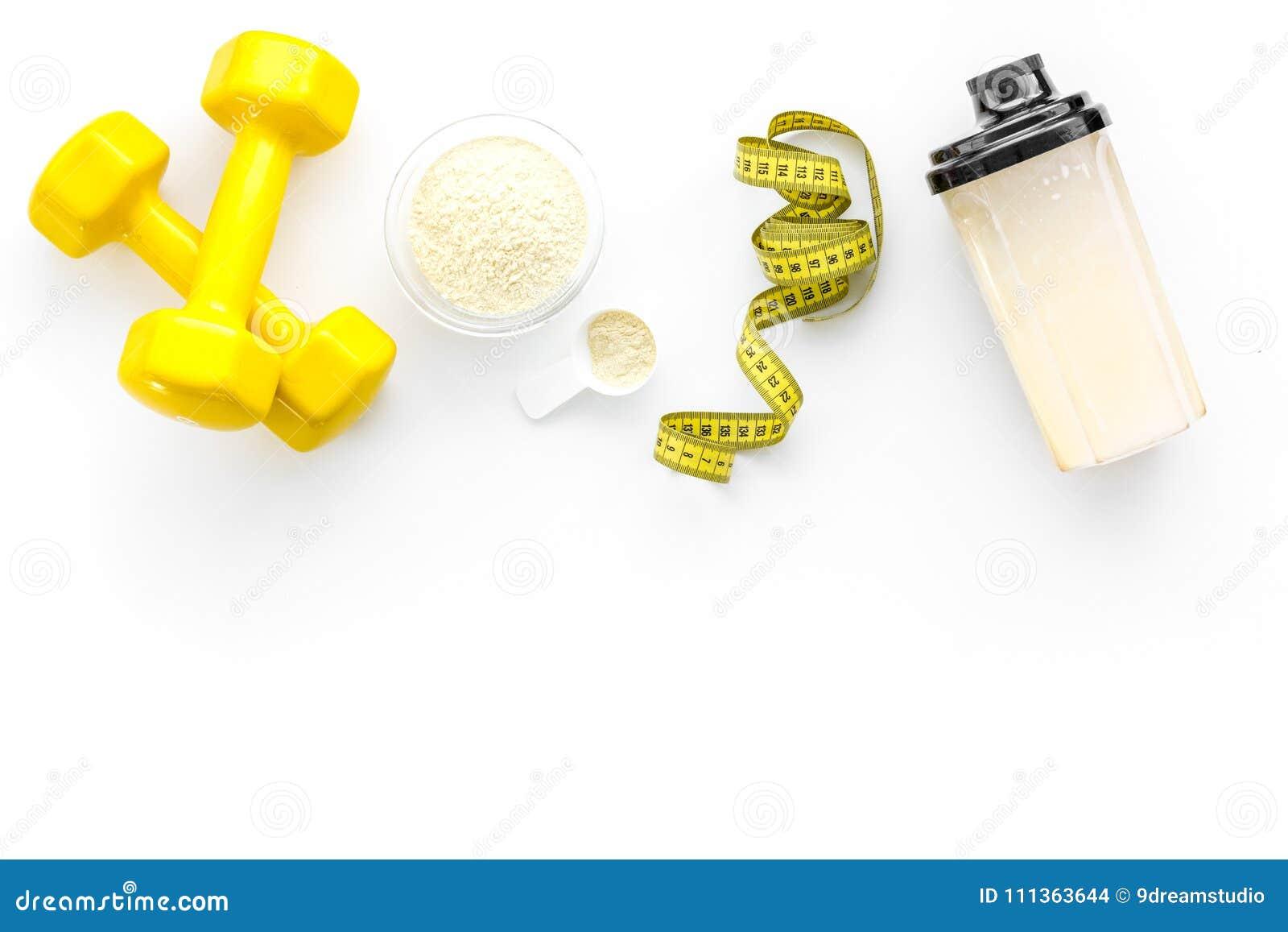 Nutrición para el crecimiento del músculo La cucharada de la proteína cerca de la coctelera y la pesa de gimnasia en la opinión s