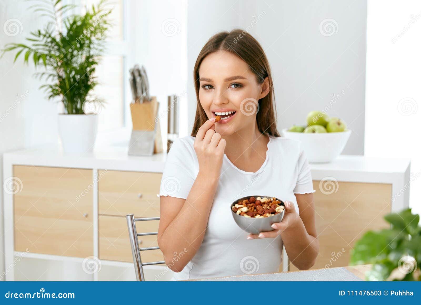 Nutrición sana Mujer joven hermosa que come nueces