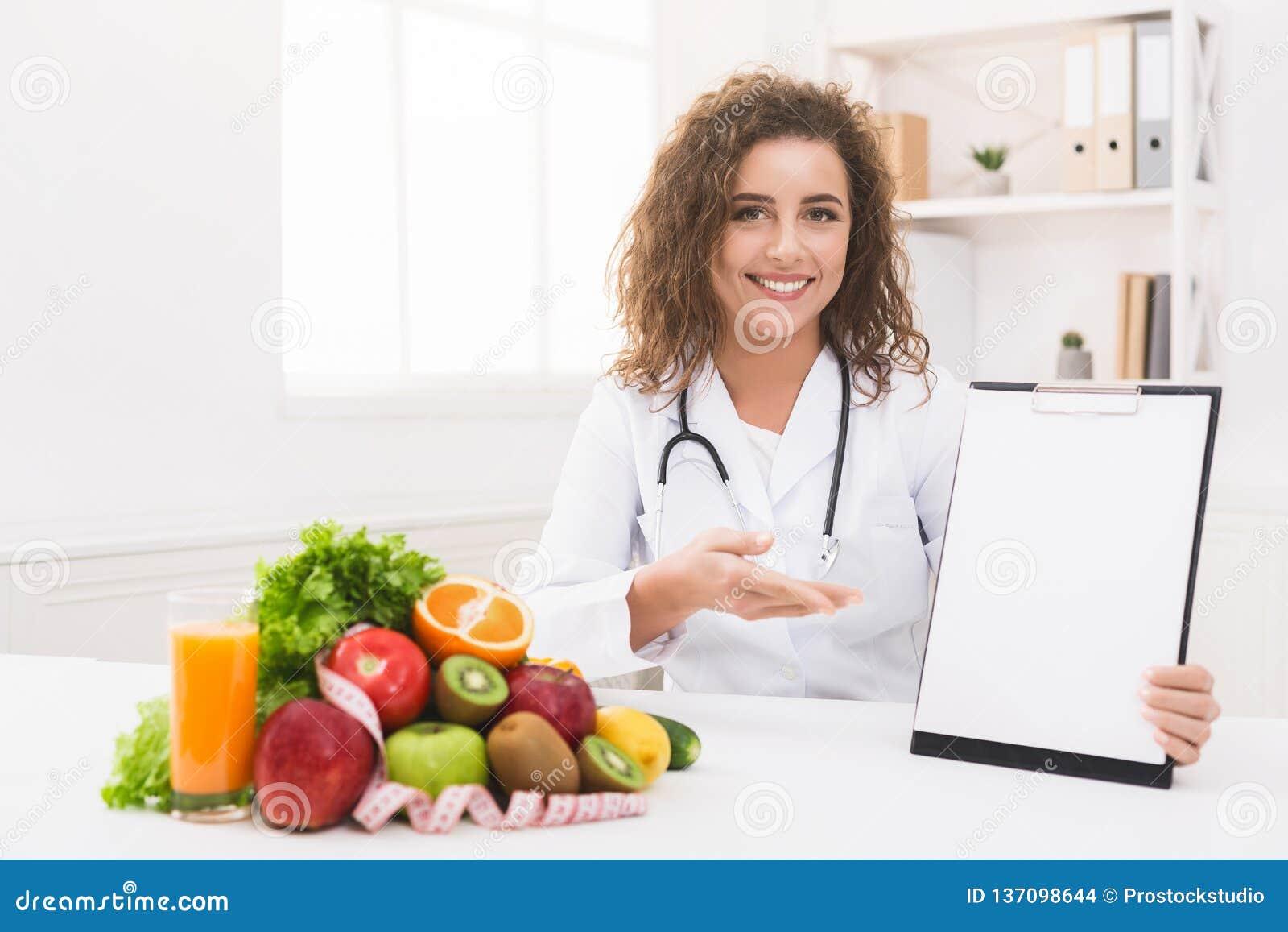 Nutricionista da mulher que aponta na prancheta vazia no escritório