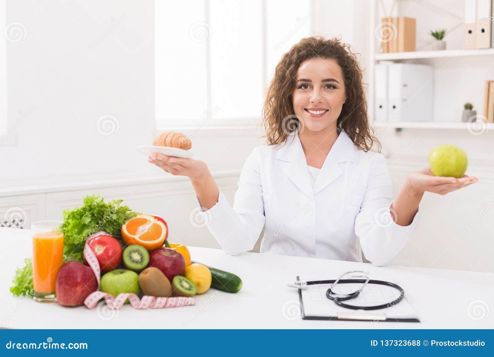 Nutricionista de la mujer que sostiene la fruta y el cruasán en manos