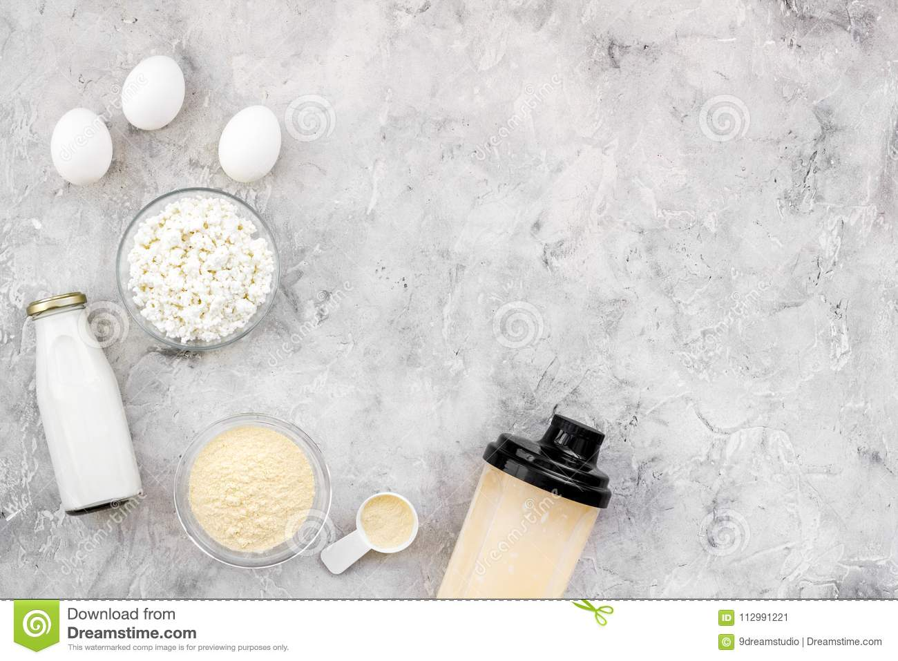 Nutrition for workout with protein cocktail, powder, eggs and milk on stone background top view mockup