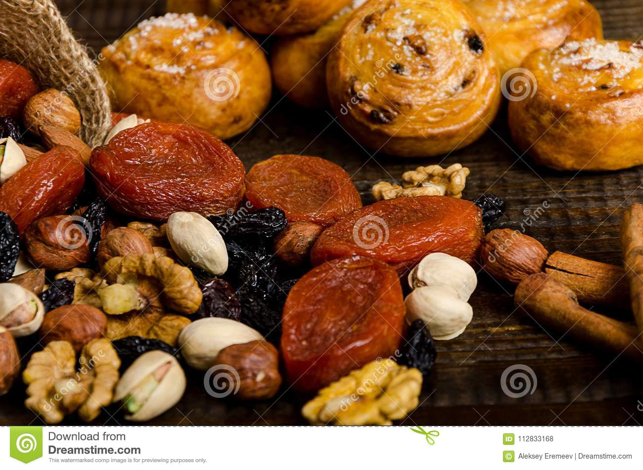 Nuts, dried fruits, pistachios and homemade cookies are scattered from the bag on the table