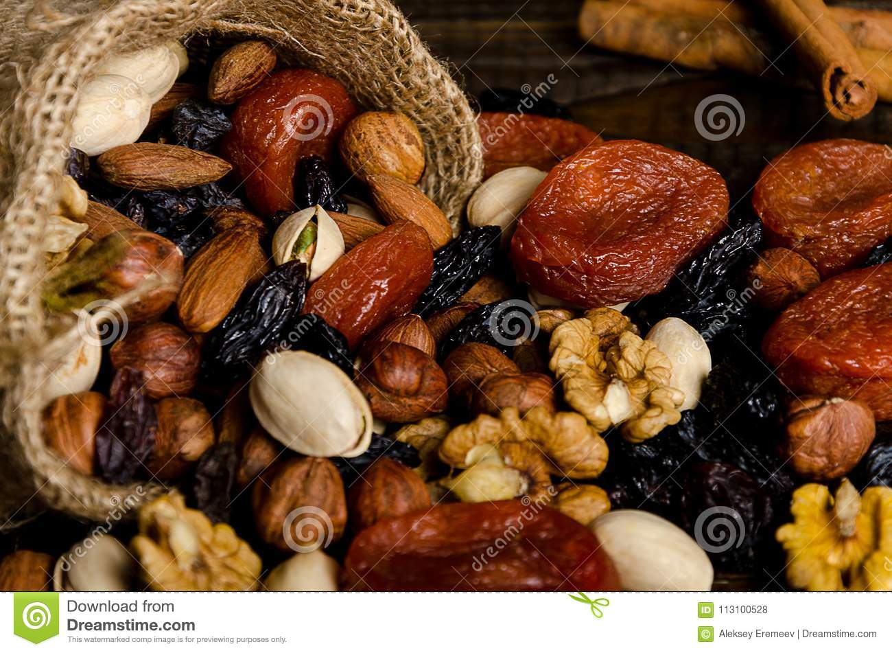 Nuts, dried fruits, pistachios and other scattered from the bag on the table