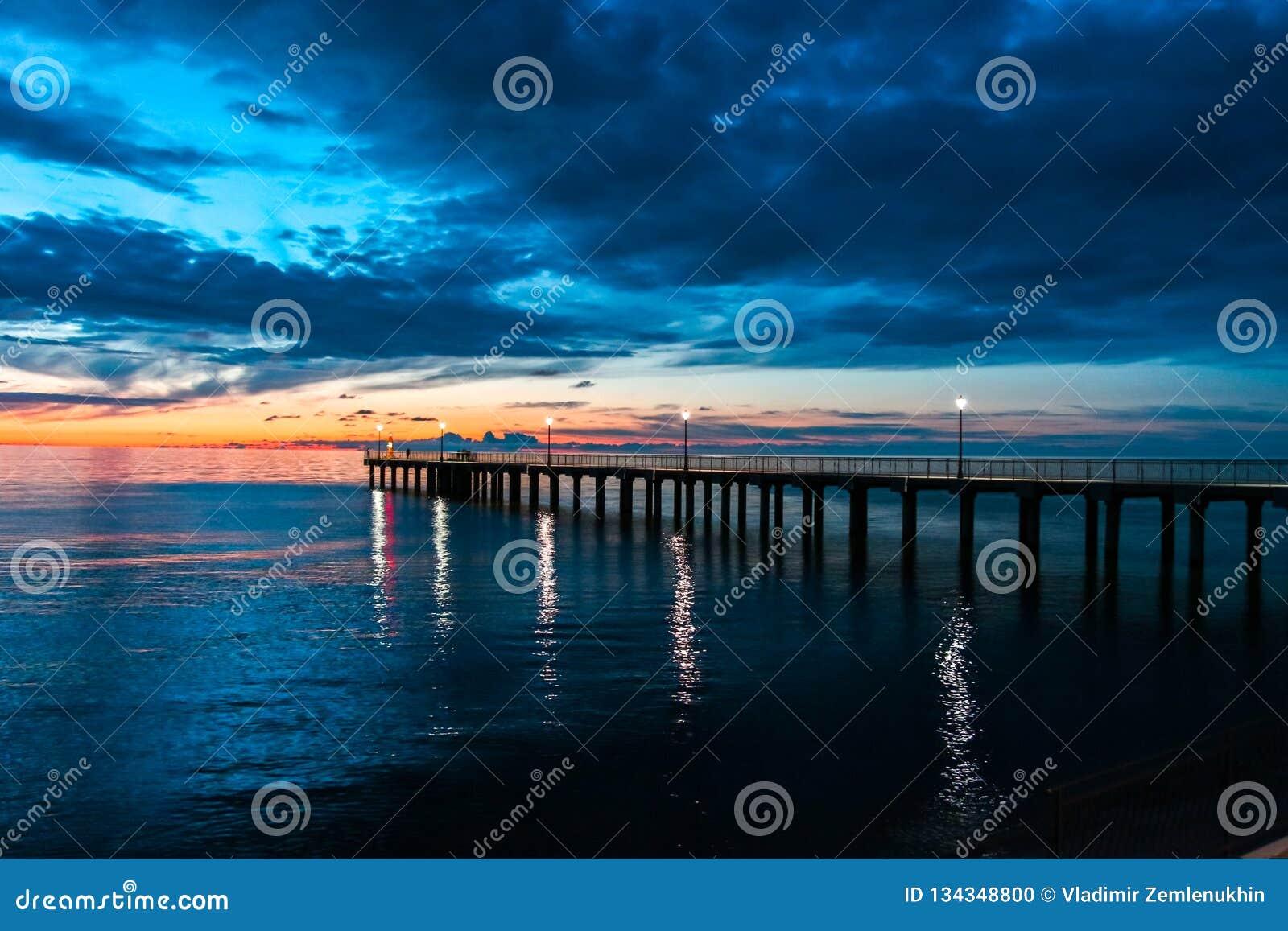 Nuvem e céu impetuosos sobre o mar no por do sol com um cais