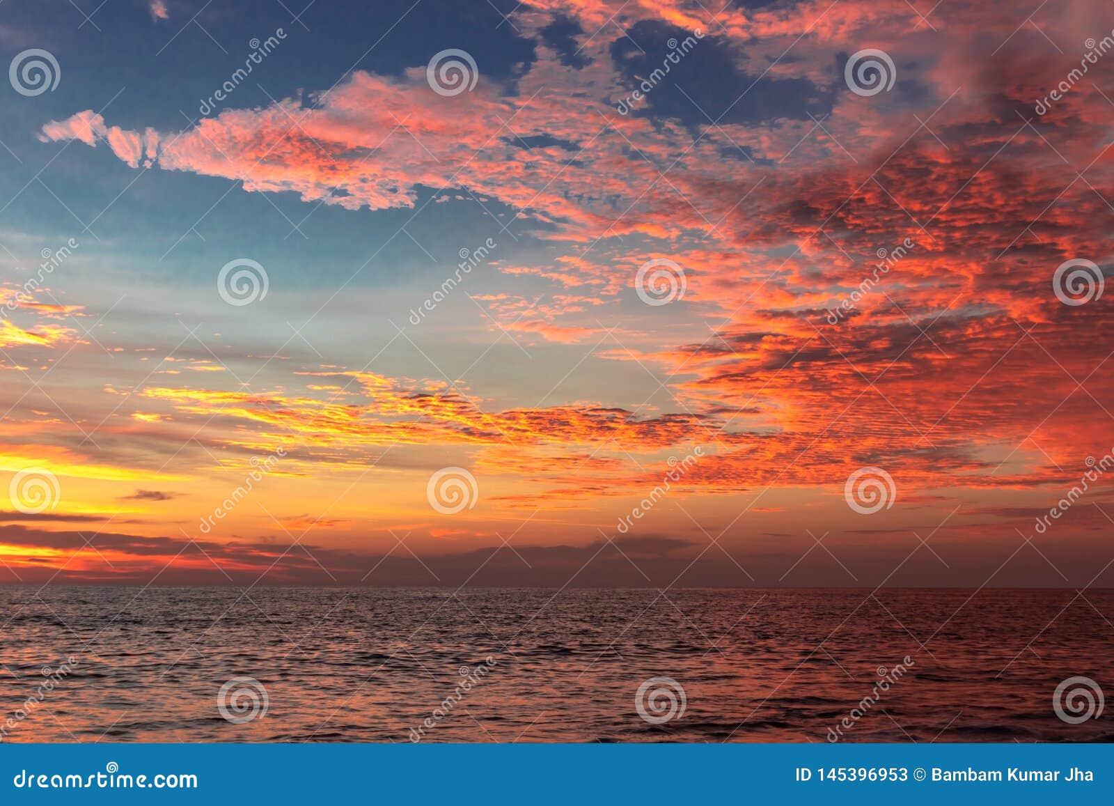 Nuvens alaranjadas do por do sol acima da água do mar