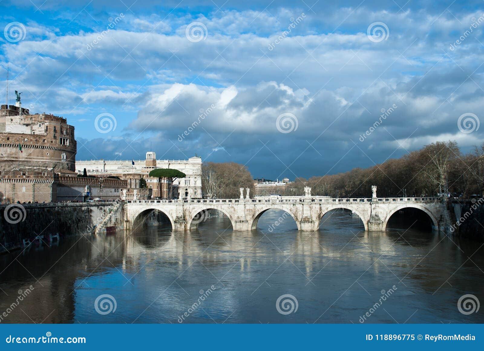 Nuvens de chuva sob o ` Angelo de Ponte Sant do rio e da ponte de Tibre próximo de Castel Sant Angelo, Roma, Itália, em fevereiro