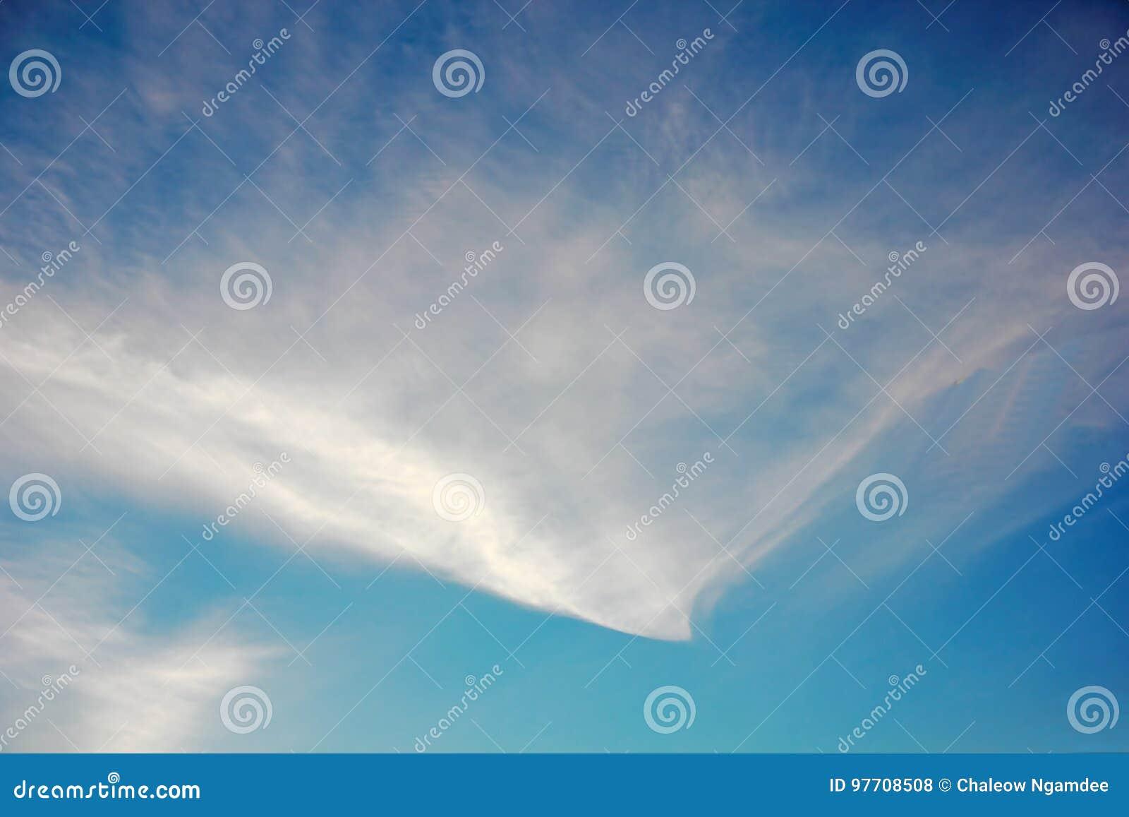 Nuvens de cirro contra a obscuridade - céu azul Para um fundo