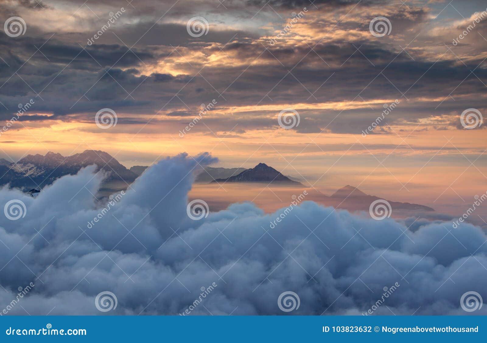 Nuvens de ondulação e montanhas irregulares na névoa de incandescência vermelha do outono