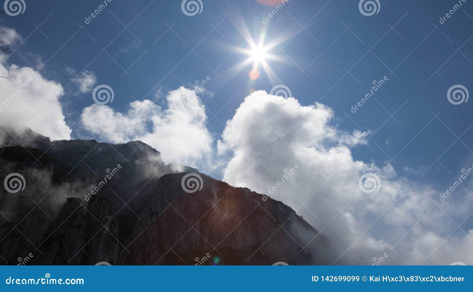 Nuvens e sol do cume da montanha