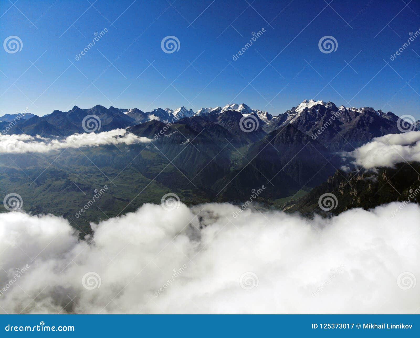 Nuvens sobre picos de montanha Névoa nas montanhas de Cáucaso
