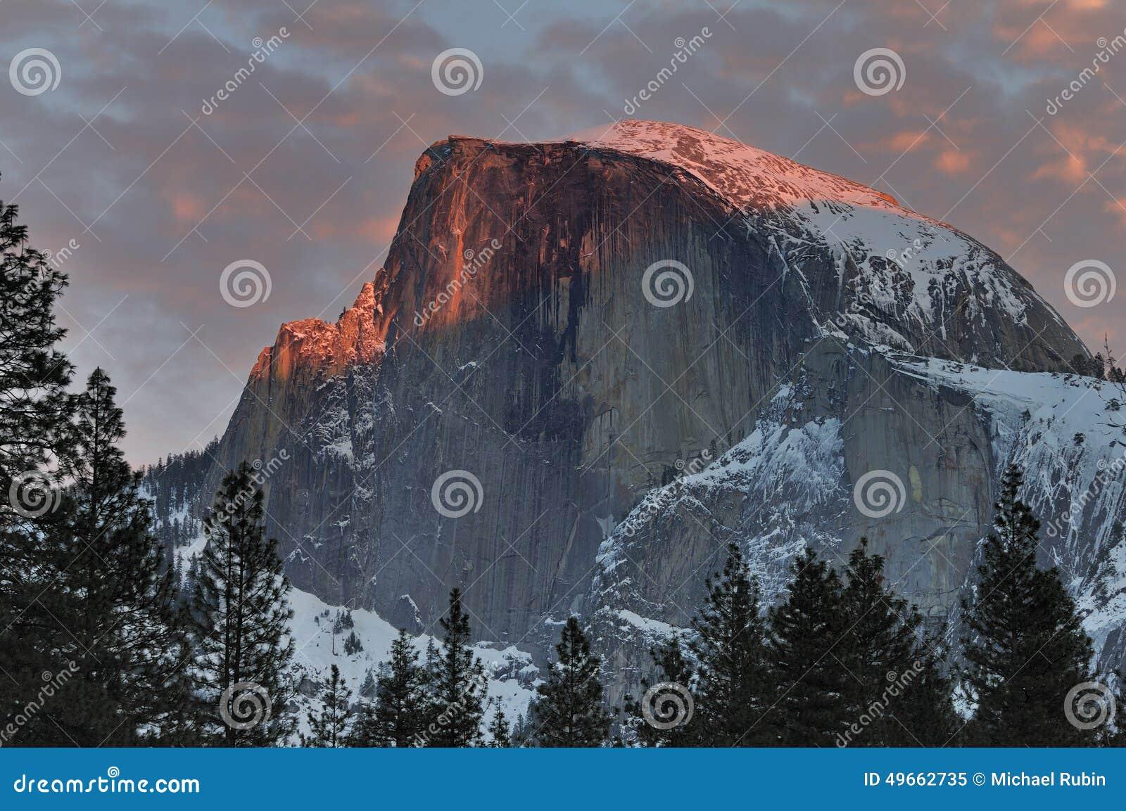 Nuvens vermelhas sobre a meia abóbada no por do sol, parque nacional de Yosemite