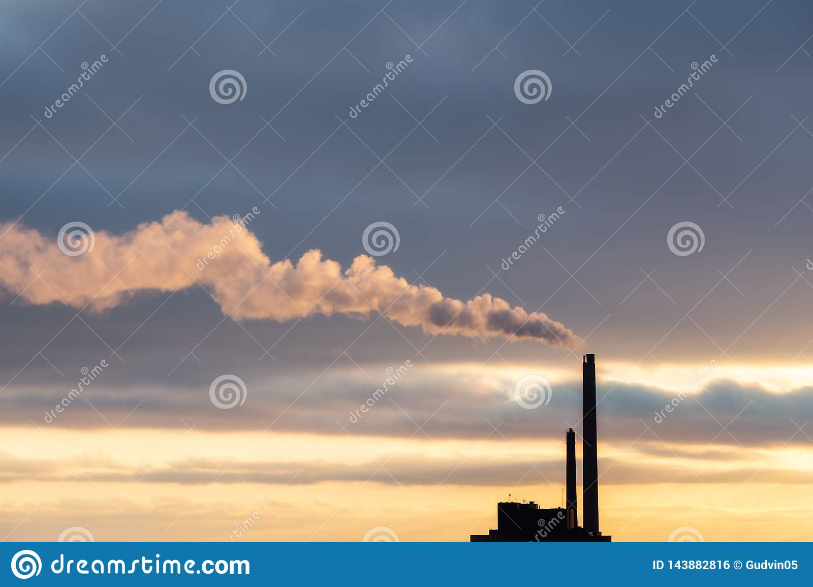 Nuvola di fumo pesante dal camino industriale nel tramonto con lo spazio della copia