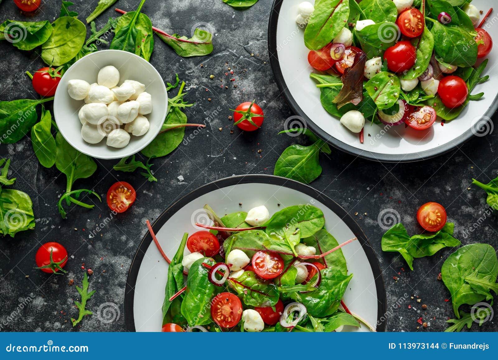 Ny Cherry Tomato, Mozzarellasallad med den gröna grönsallatblandningen och den röda löken tjänat som på plattan sund mat
