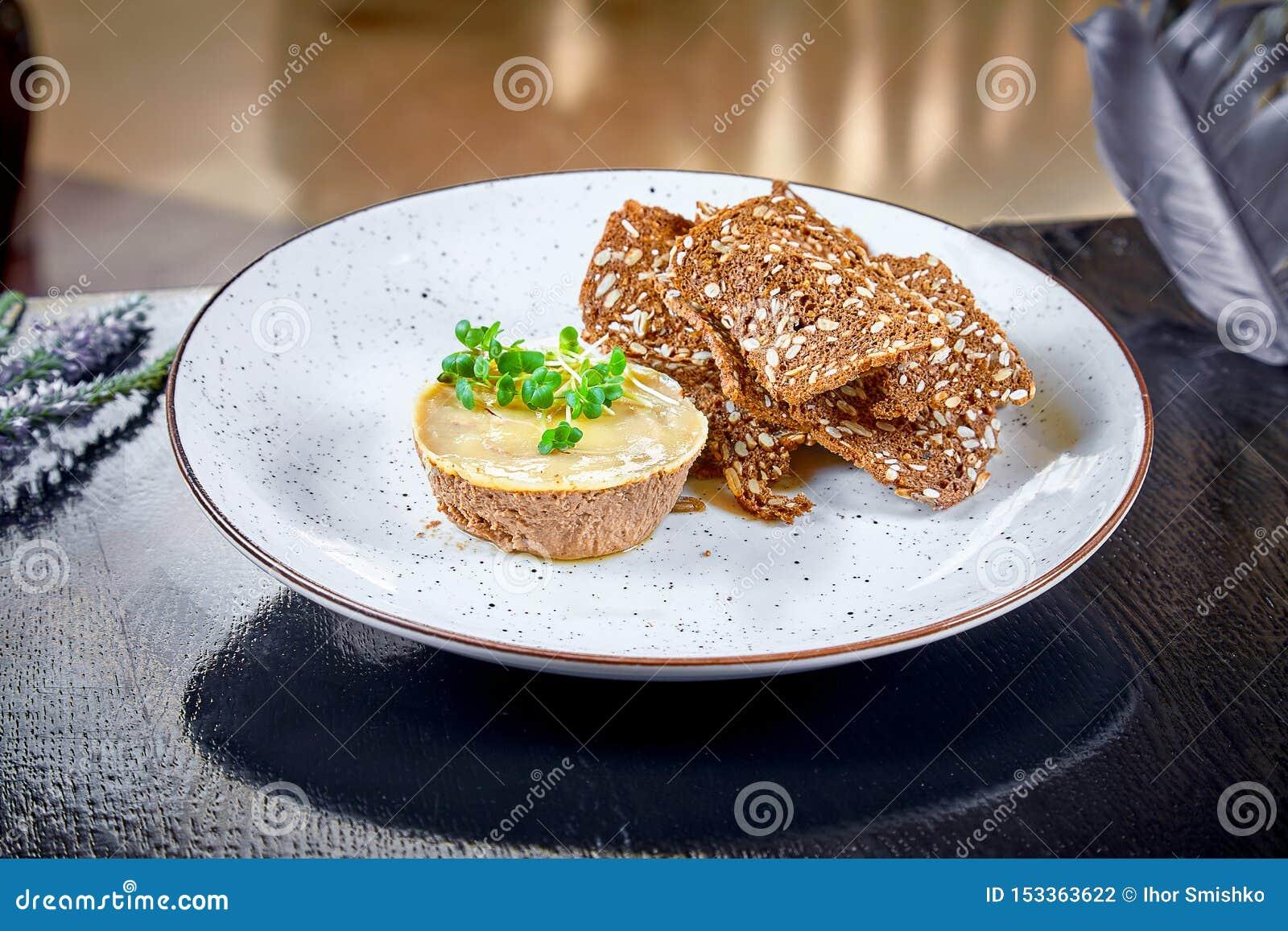 Ny hemlagad höna- eller andleverpate med bröd, krutonger på den vita plattan Stranda av h?r v?nder mot in Kopieringsutrymme som ?