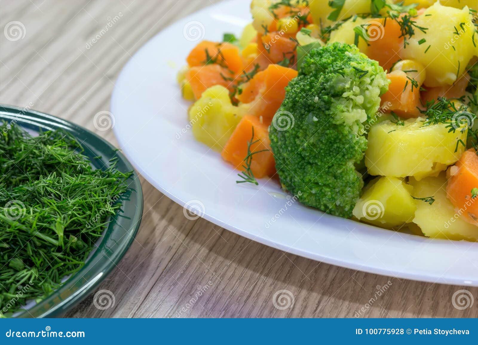 Ny huggen av dill och ångade grönsaker - potatisar, morötter, broccoli, havre äta som är sunt