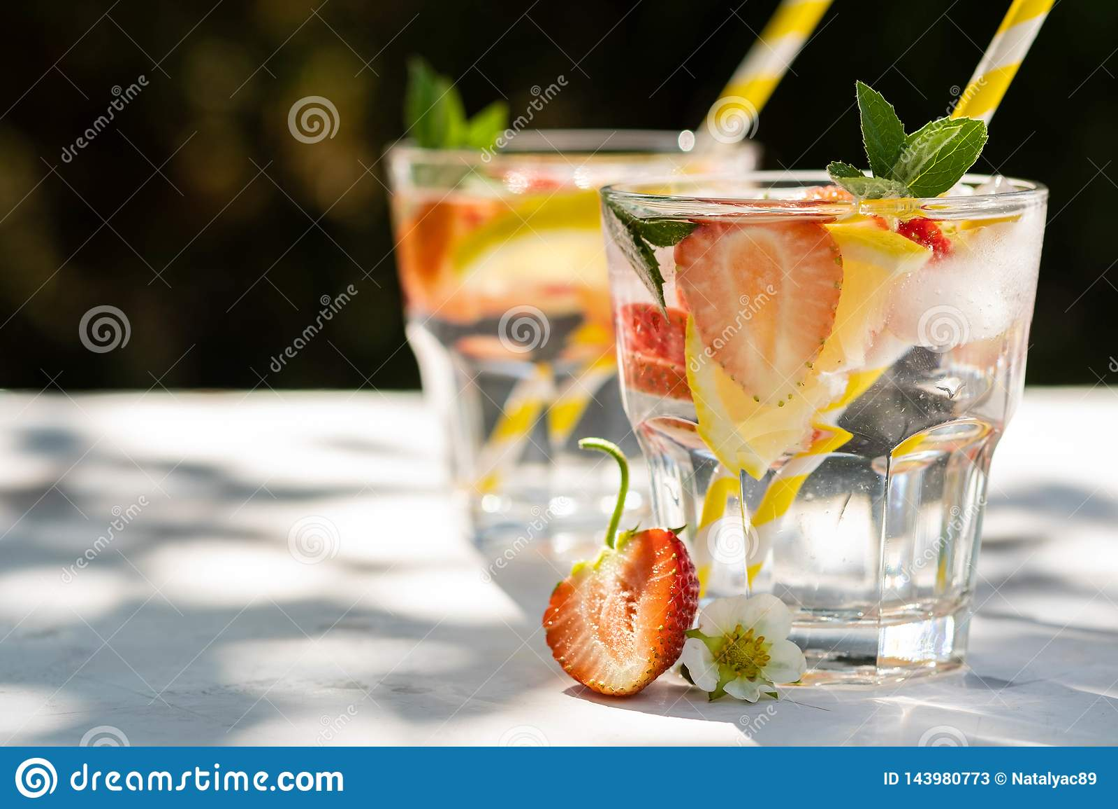 Ny jordgubbe för coctail Ny sommarcoctail med jordgubbe- och iskuber Exponeringsglas av jordgubbesodavattendrinken på mörker