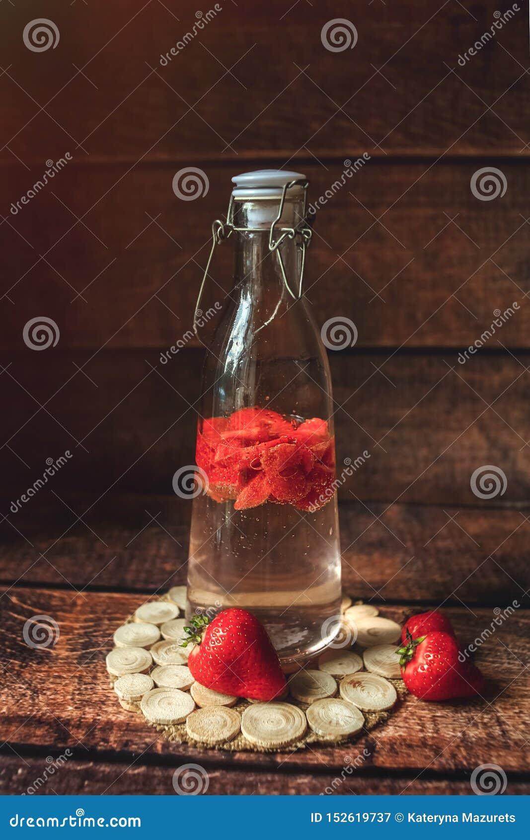 Ny jordgubbe i flaska med vatten, lemonad, vitaminedrink, ecodeco som tonas