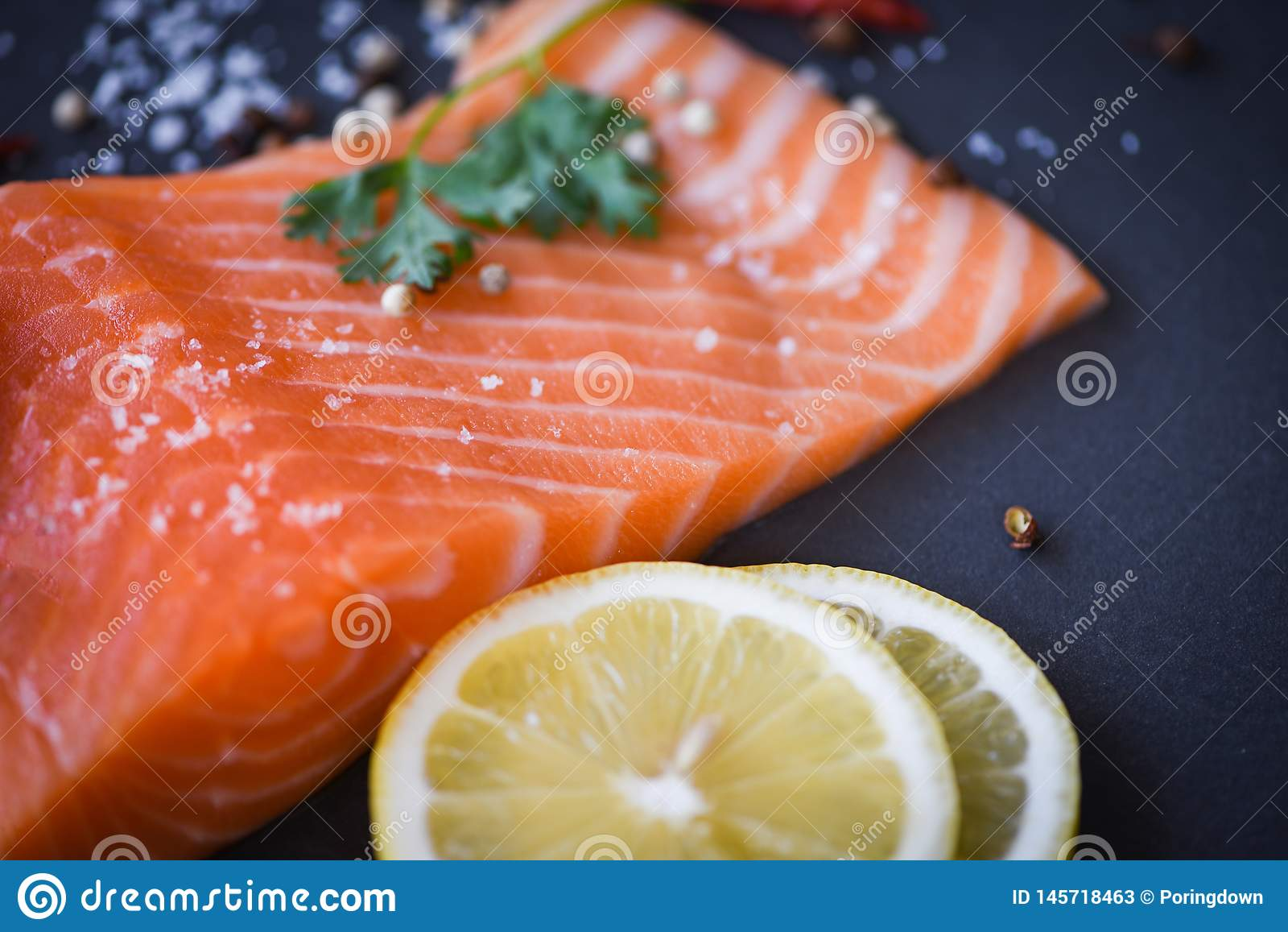 Ny laxfil? p? m?rkt bakgrundsslut upp av r? laxfiskskaldjur med citron?rter och kryddor