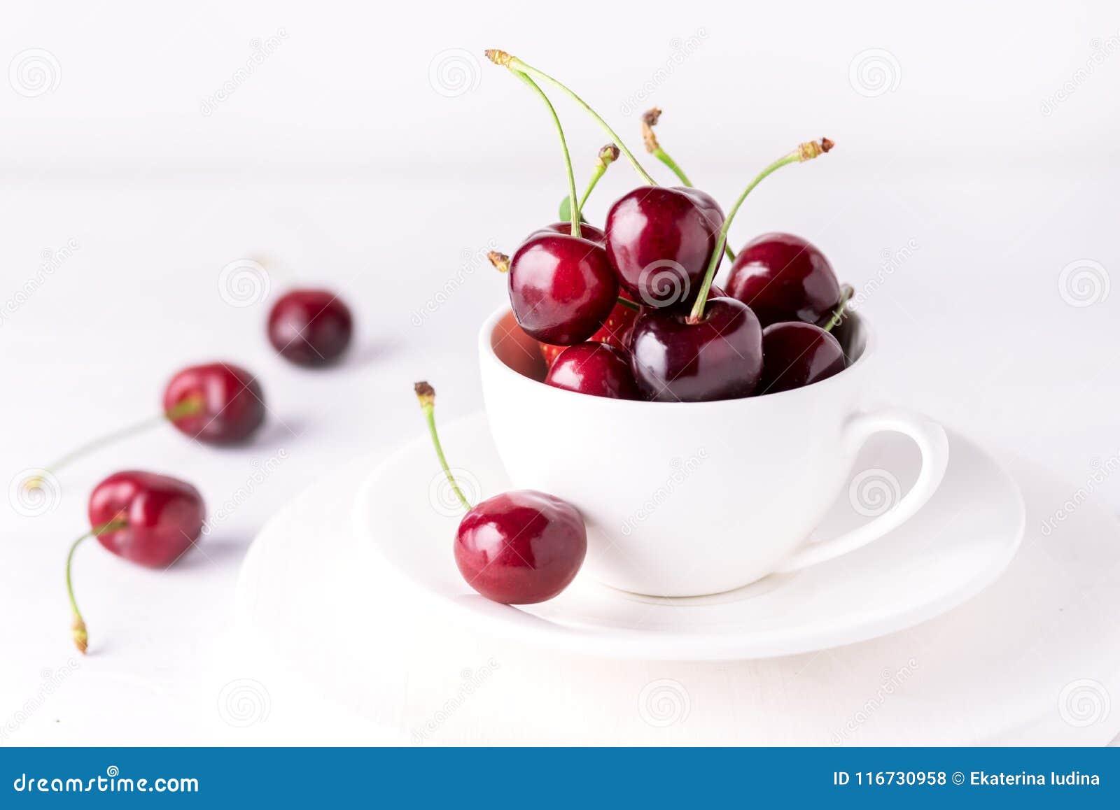 Ny och härlig körsbär i en vit kopp mogna saftiga Cherry Close Up White Background