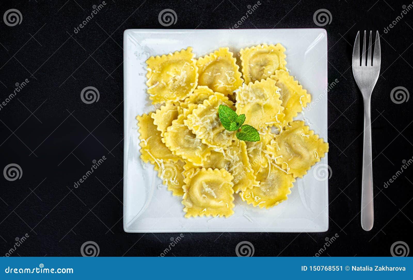 Ny ravioli på en vit platta över mörk bakgrund, bästa sikt ItalienareRaviolli slut upp kopiera avst?nd