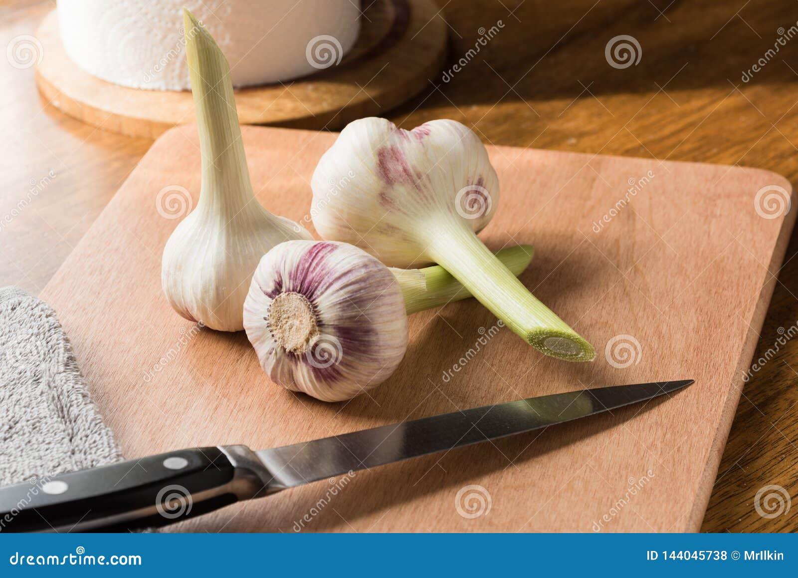 Ny ung vitlök och kniv på köksbordet
