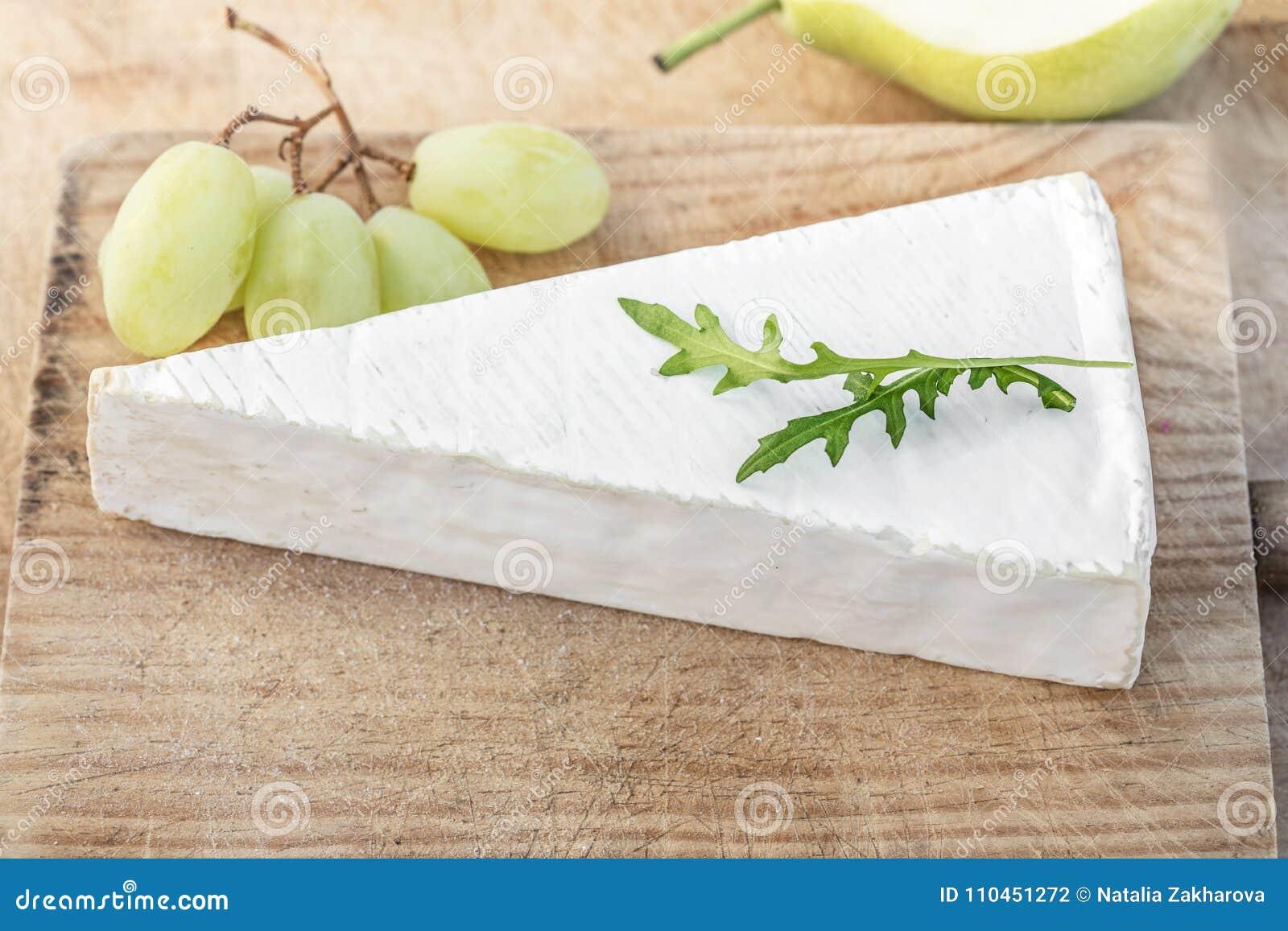 Nya Brie Cheese på skärbräda med druvor och frukter, överkant