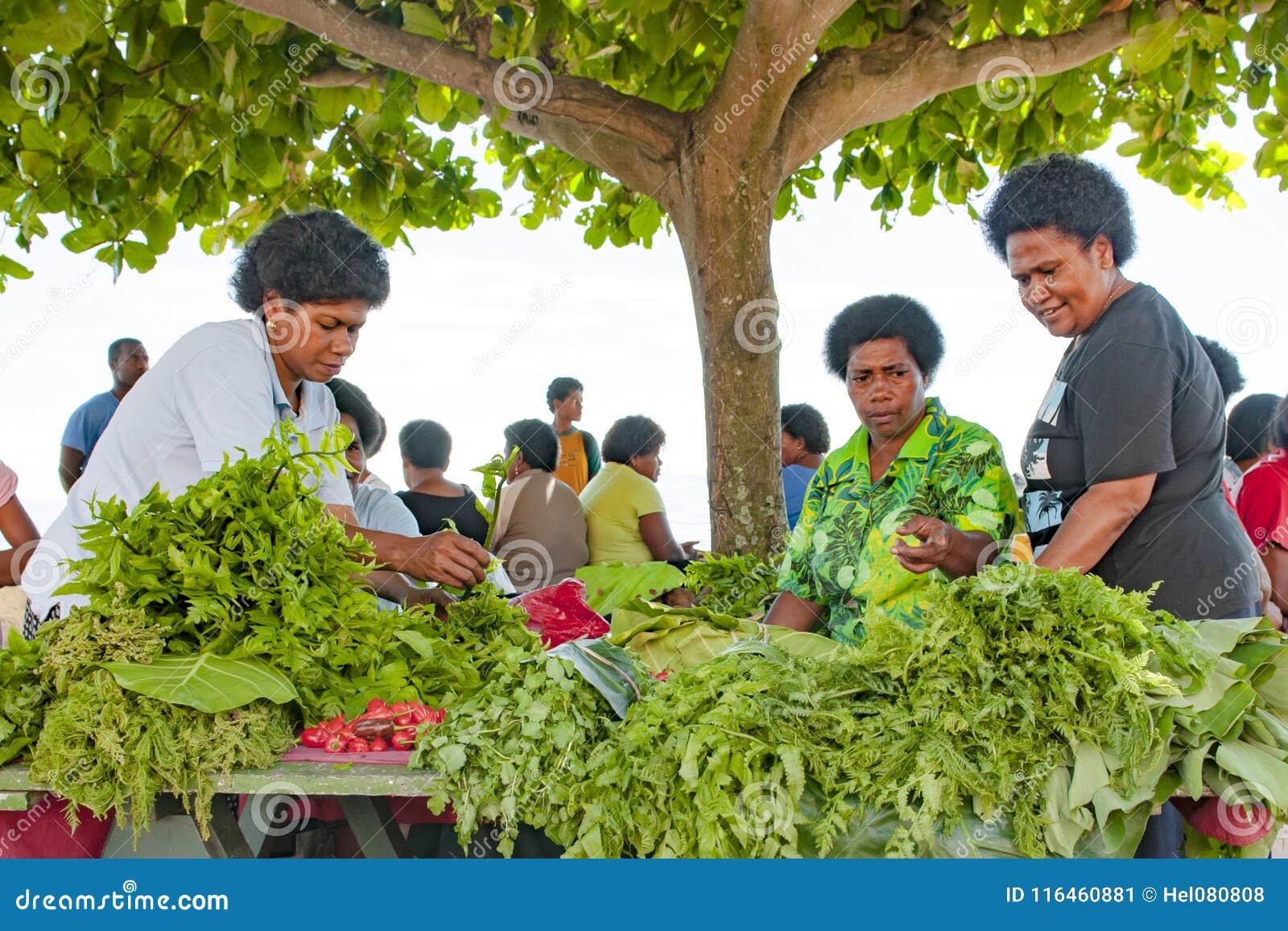 Nya grön sallad och grönsaker i skugga av sidor av ett träd på tropisk marknad på ön i Stilla havet
