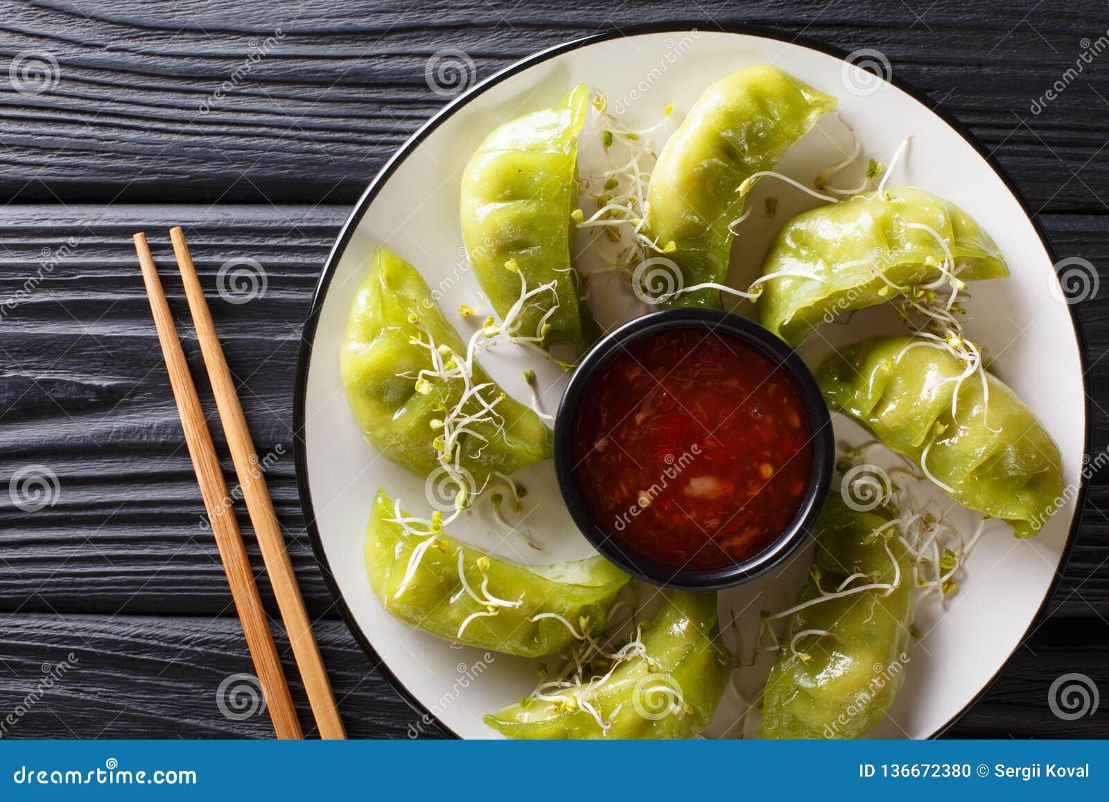Nya gröna gyozaklimpar med matcha tjänas som med kryddig chilisås och microgreen närbild på tabellen horisontalöverkant