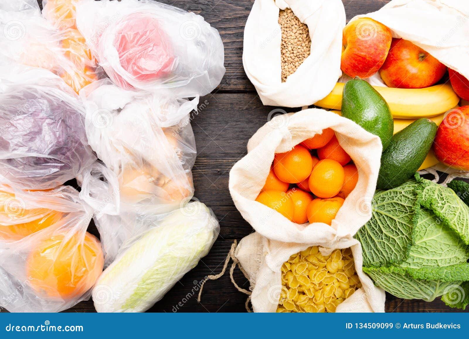 Nya grönsaker och frukter i ecobomullspåsar mot grönsaker i plastpåsar Nollförlorat begrepp - bruksplastpåsar eller mång-