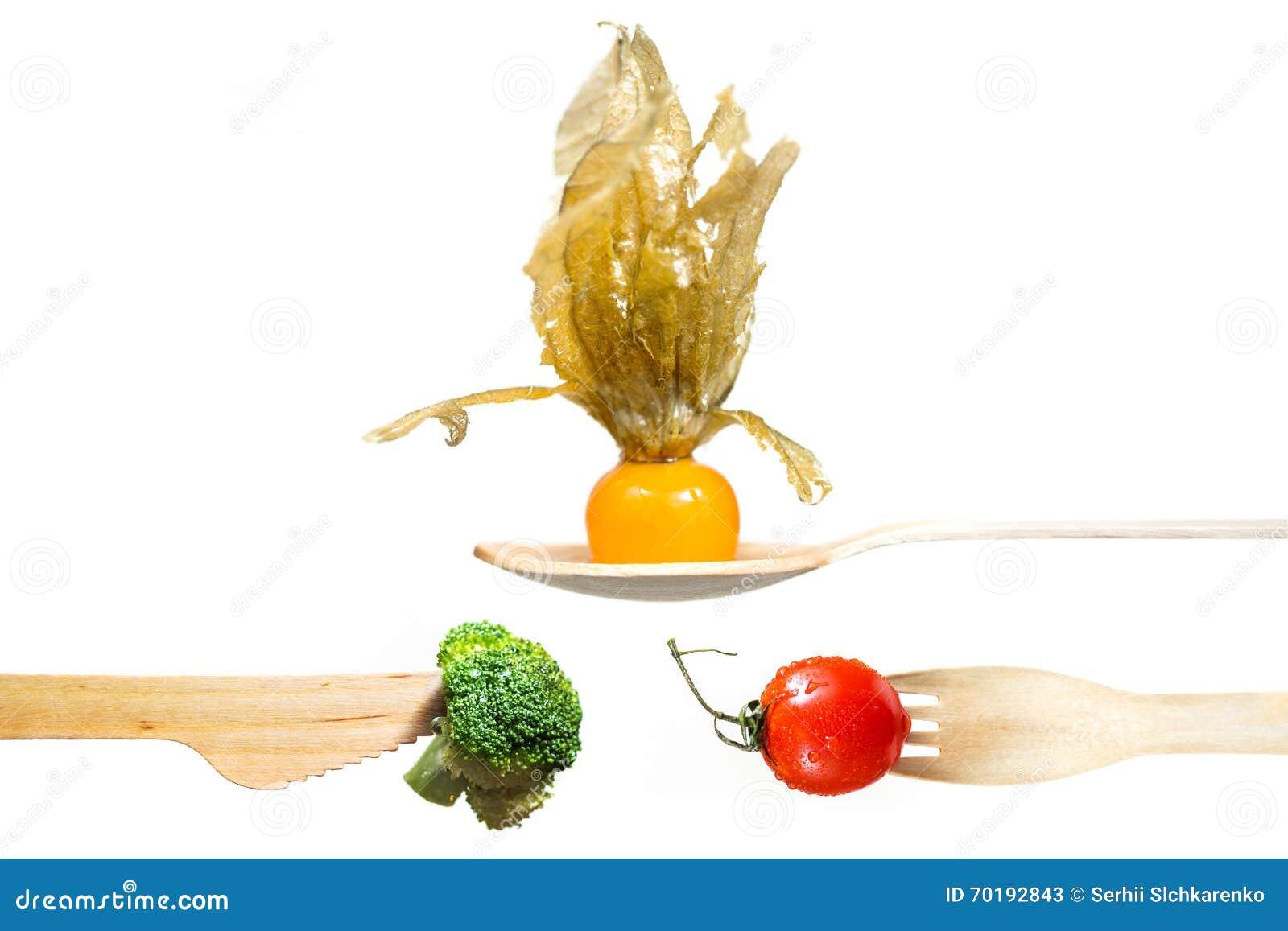 Nya grönsaker tomat, broccoli, physalis på trägaffeln, kniv, sked