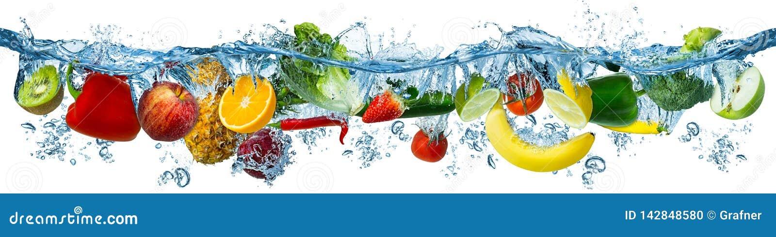 Nya mång- frukter och grönsaker som plaskar in i blå klar vattenfärgstänk som, sund mat bantar friskhetbegrepp, isolerade vitt