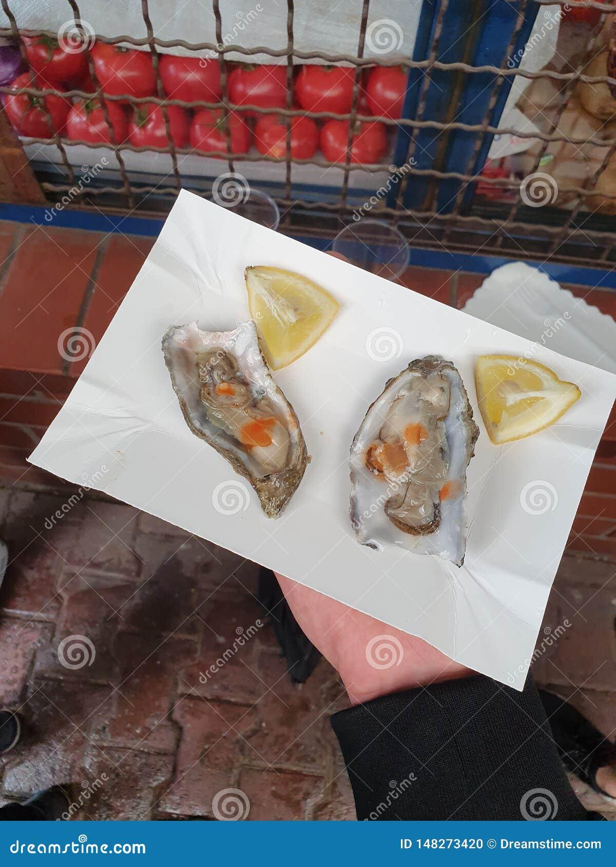Nya ostron p? en platta med tabasco och citronen
