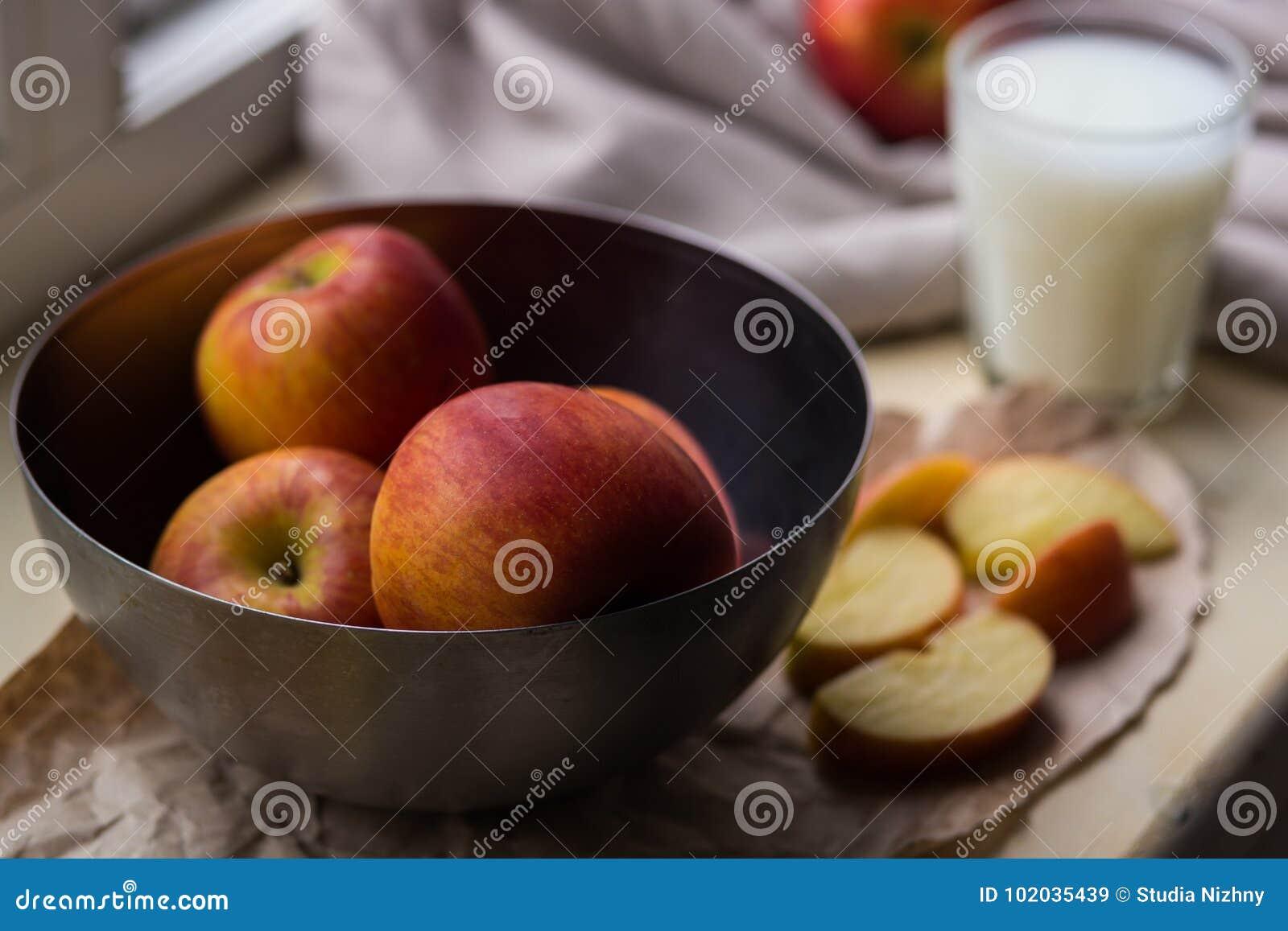 Nya röda äpplen i ett stilfullt järn besegrar att ligga på en vit fönsterfönsterbräda Apple skivor och ett exponeringsglas av mjö