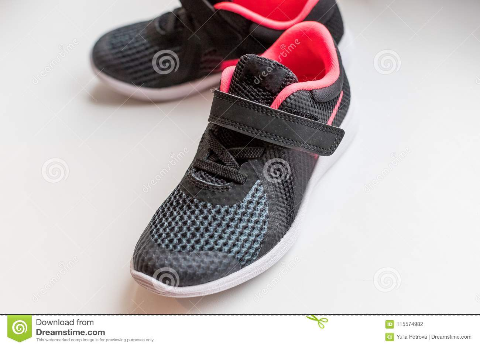 Nya rosa färger, svarta sportskor på vit bakgrund lurar rinnande skor Rinnande skor för barn` s På a
