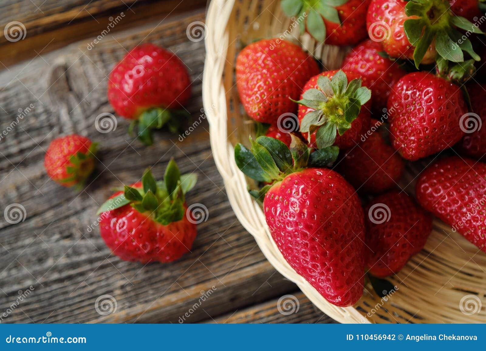 Nya saftiga jordgubbar i en träkorg på tabellen