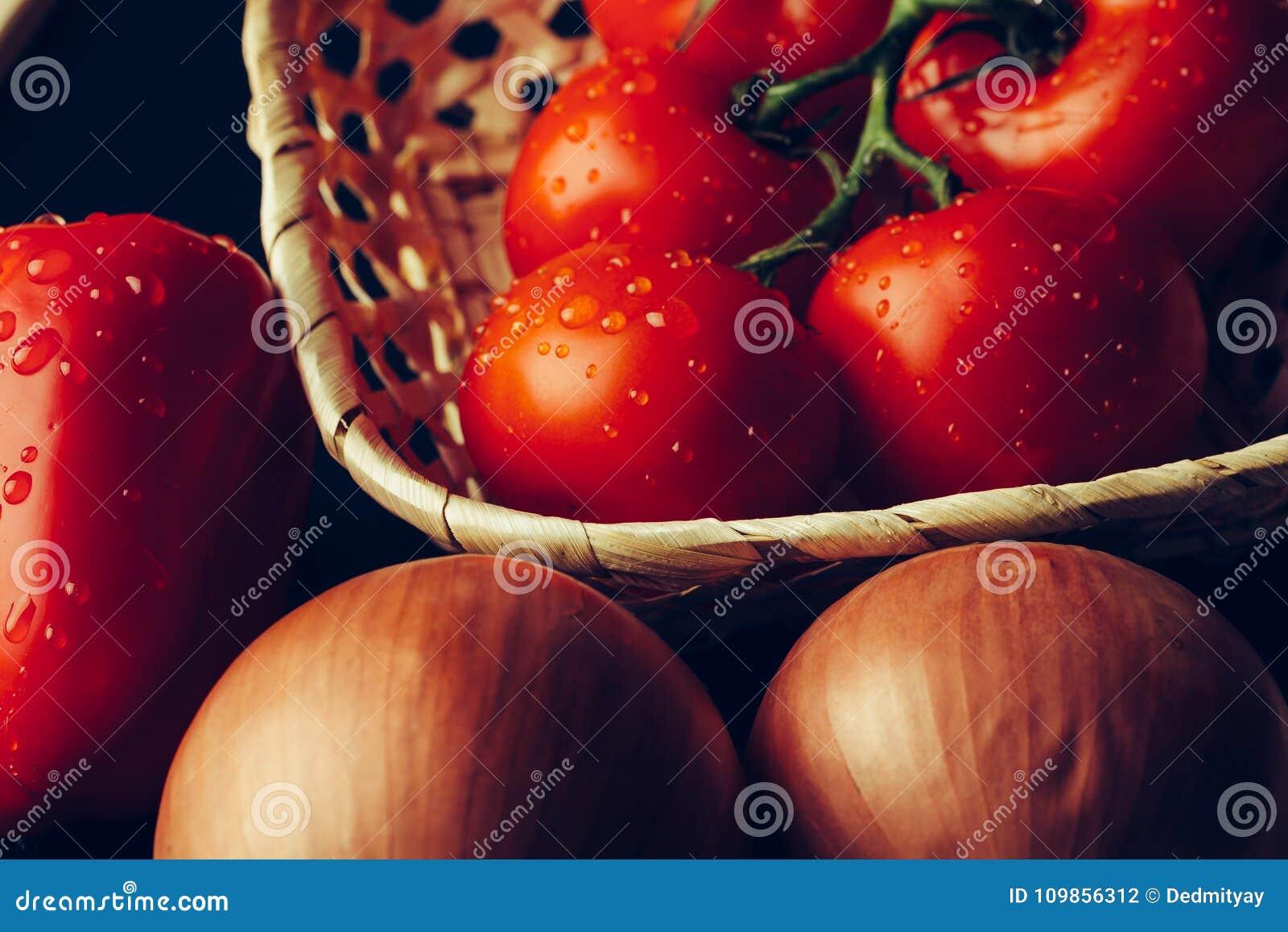 Nya våta tomater i droppar av vatten, guld- lök, spansk peppar på mörk bakgrund