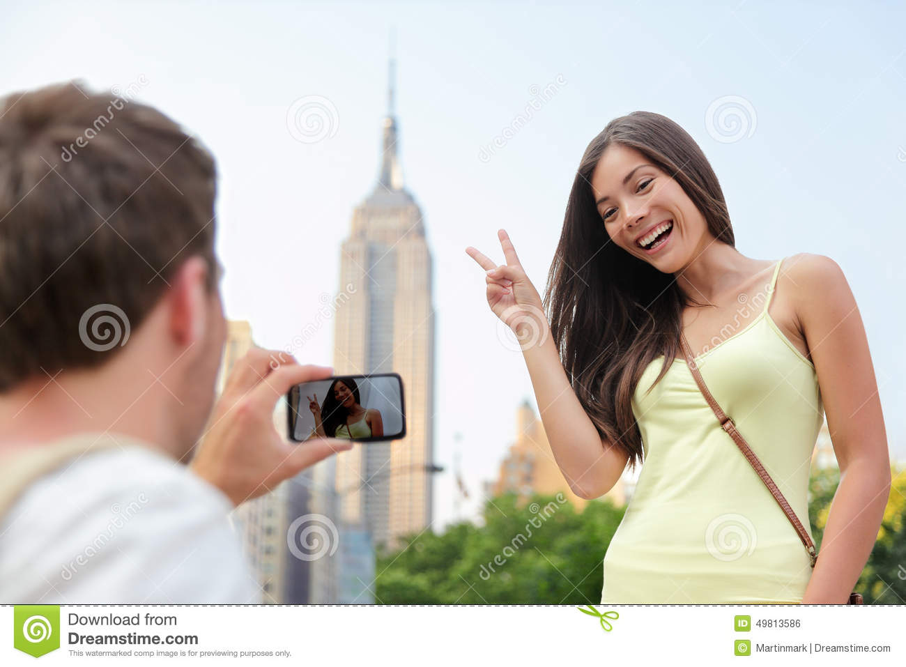 NYC asian tourist posing at Empire State Building. Editorial Stock Photo