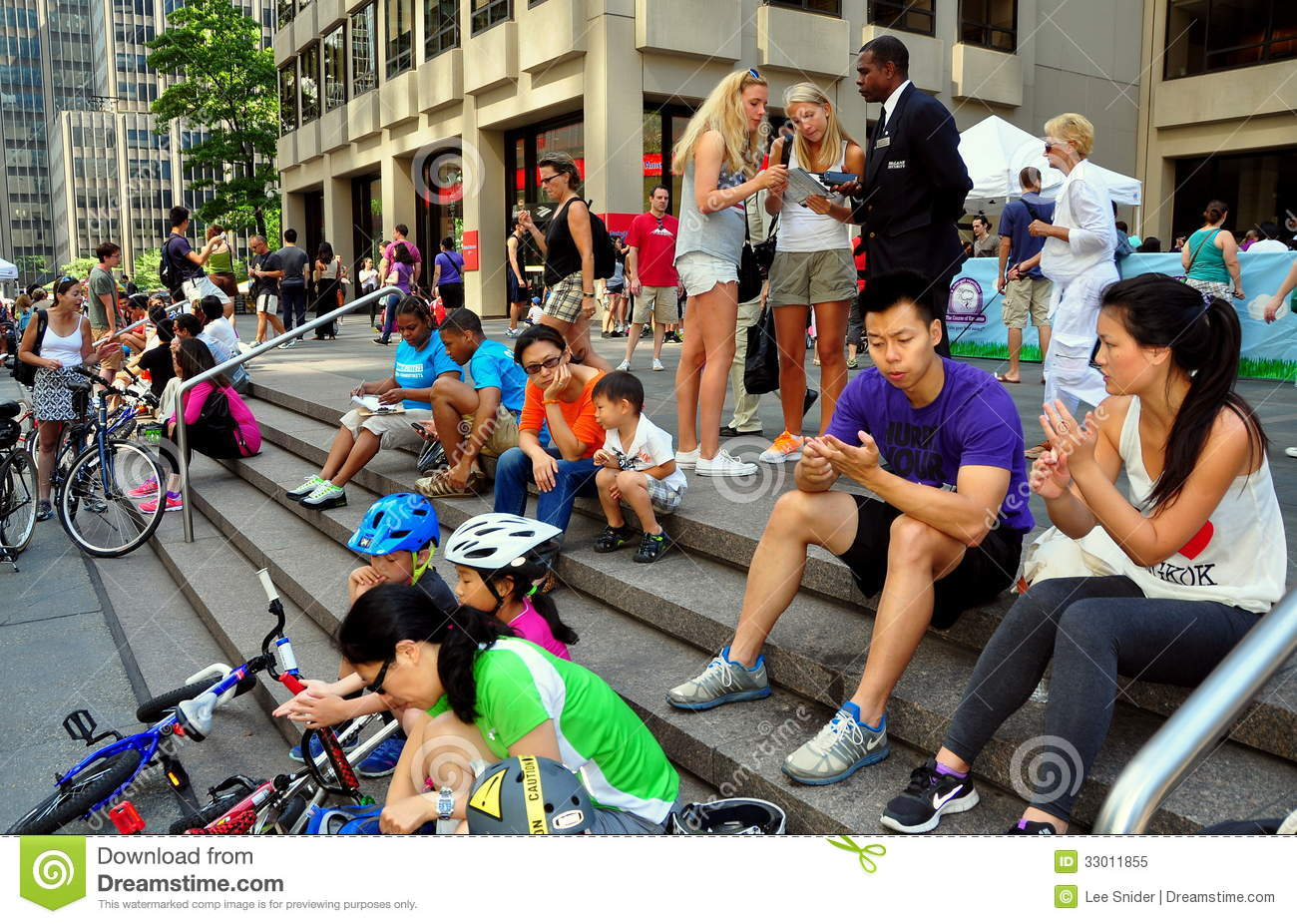 People, some with their bicycles, relaxing on the steps of a Park ...