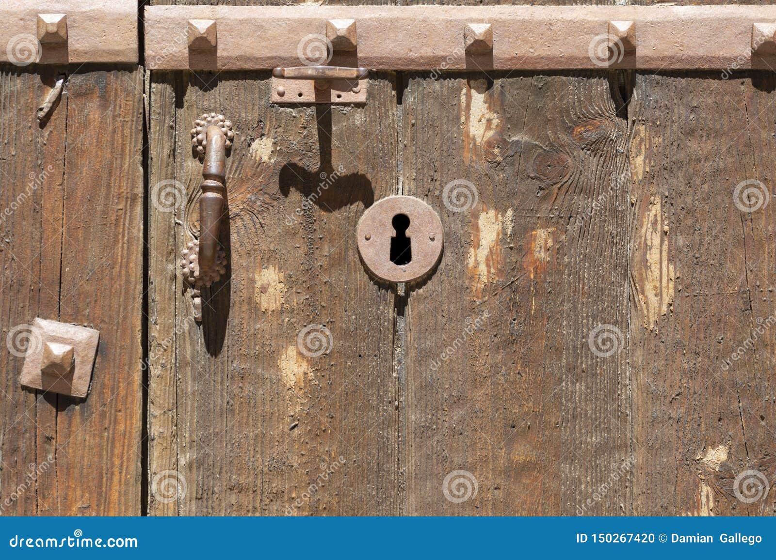 Nyckelhål i en gammal paneled trädörr med det antika dörrhandtaget;