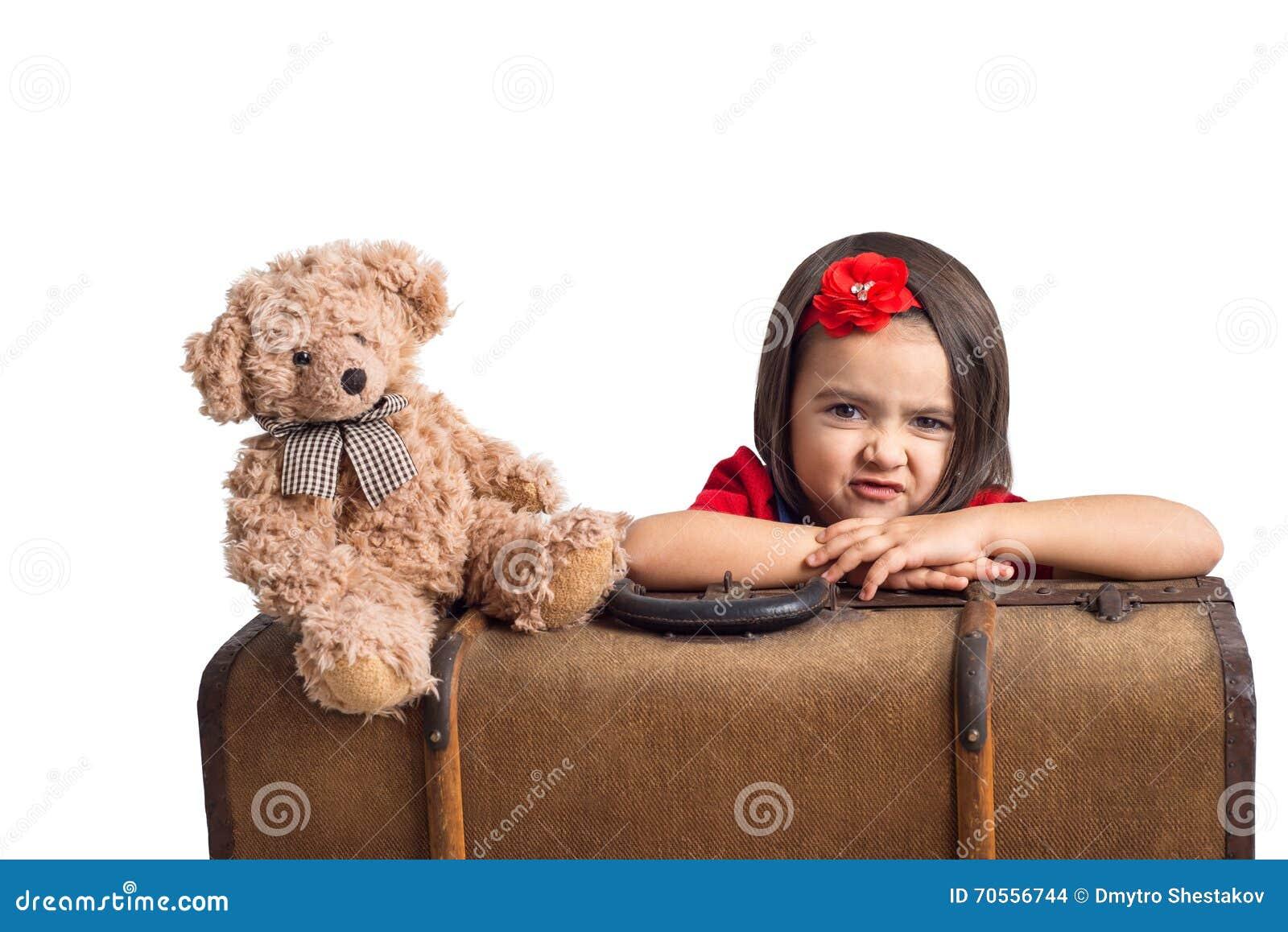 Nyckfull liten flicka med resväska- och leksakbjörnen