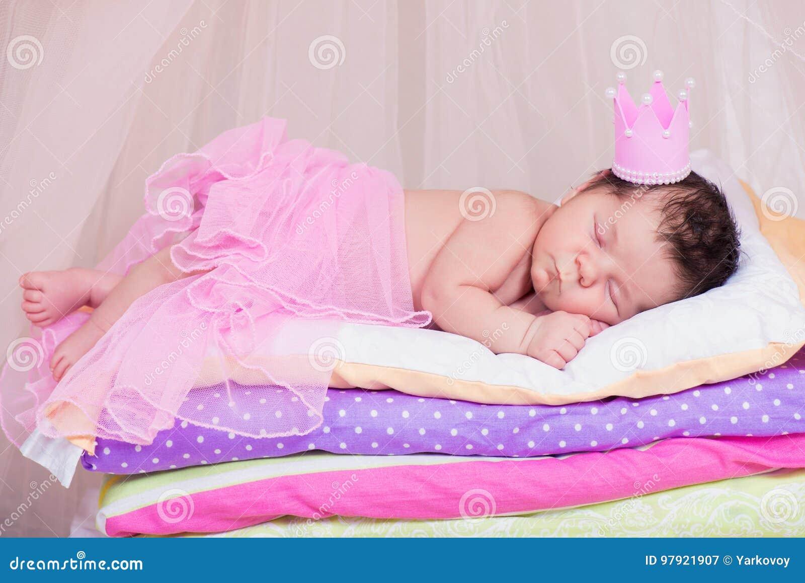 Nyfött behandla som ett barn flickan i en krona som sover på sängen av madrasser Felik prinsessa och ärtan