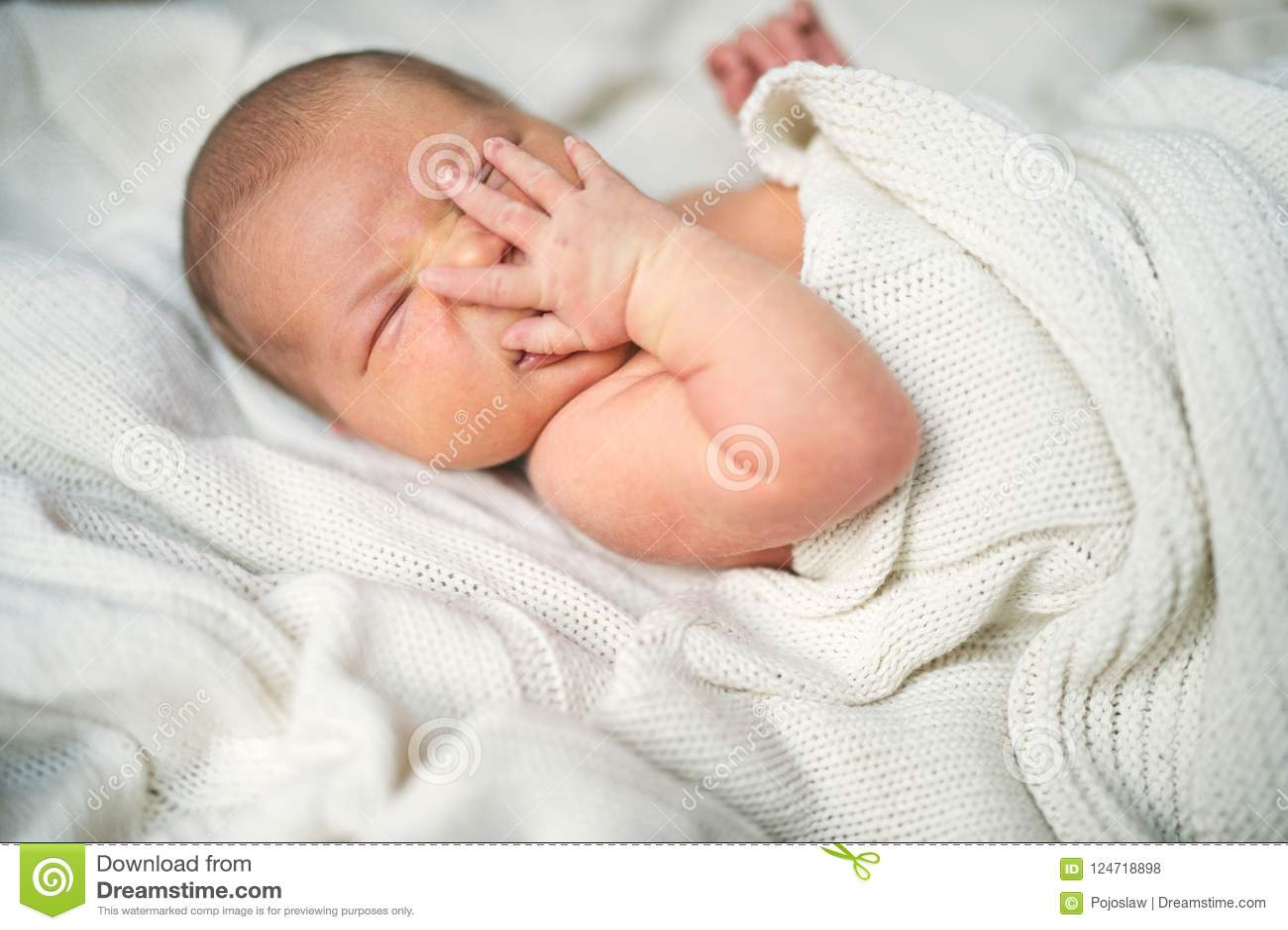 Nyfött behandla som ett barn med en hand på hennes framsida som ligger på säng som är dold vid en vit filt